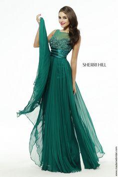 New for 2015...Yards of deluxe fabric array the A-line silhouette of Sherri Hill 4809 prom dress, capped with a sheer yoke defining the illusion bateau neckline. Lace defines the sweetheart bodice, cinched with a trio of satin bands running from the under bust toward the natural waist. From there, the shirred skirt plummets into the full length, finished with an overskirt draping gracefully on either side.