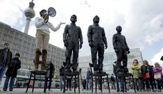 "A women delivers a speech as she stands on a chair of the public art project ""Anything to Say?"" at the Alexander Square in Berlin, Germany, Friday, May 1, 2015. The sculpture of the Italian artist Davide Dormino shows the whistleblowers Chelsea Manning, Julian Assange and Edward Snowden, from right, to honour their courage."