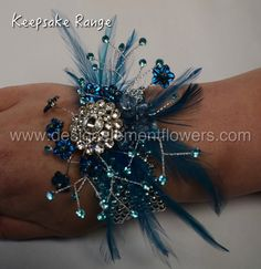 Stunning Wrist Corsage is handcrafted with Aquamarine Feathers,Diamantes Brooch and Flowers which is created on a Silver Pearl Bracelet. www.designelementflowers.com