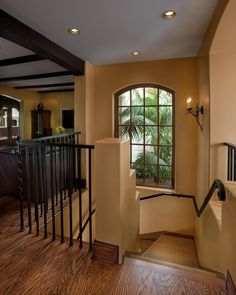 A+wrought+iron+railing+provides+lovely+contrast+to+the+warm+neutral+tones+of+the+staircase.+A+slightly+arched+window+fills+the+space+with+essential+light,+with+recessed+lighting+and+a+wrought+iron+sconce+to+offer+light+in+the+evening+hours.