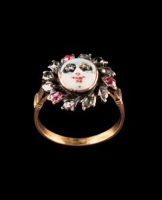 As one of the chief amusements of society, the masquerade provided a theme. This gold and silver ring circa 1750 displays a face covered by a white mask, eyes set with rose-cut diamonds, surrounded by an open border of rubies and diamonds in petal-shaped collets.