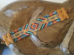 Native American inspired hand loomed beaded bracelet. All the colors of the rainbow. The darker blue and the gold make the bracelet sparkle with every movement. Leather end tabs and gold clasp. Quality made and very durable will give you many years of enjoyment Measures 7 1/2 inches in total length including the leather end tabs and gold clasp. Beaded portion measures 4 inches. It is 7/8 inches wide. It will fit a wrist size of 6 - 7 inches. If need be more loops can be added to t...