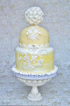 A spring wedding cake made with yellow a fondant exterior crowned with a dome top and adorned with edible hand crafted hydrangea flowers and hand cut damask style scroll work.