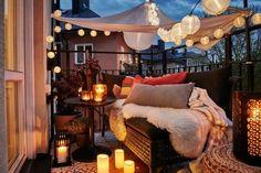 decoration balcon, petit canapé noir, coussins décoratifs, lanternes à bougies