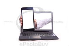 Woman hand holding mobile phone and coming out of laptop