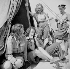 Flakhelferin prisoners. Note the pants (the young woman standing) with side openings for staffing women's auxiliaries of the Luftwaffe. Also, check what seems to be an ATS gal!