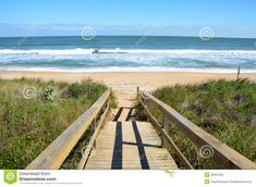 st. augustine beach  | Scenic view of waves breaking on sandy beach with wooden boardwalk ...