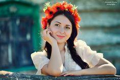 Девушка с венком из красных маков на голове стоит опираясь на деревянную перекладину, правую руку держит у лица и загадочно смотрит на нас. Фотограф Александр Друкар
