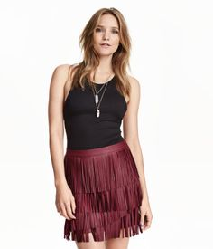 Short skirt in imitation leather with fringe and concealed side zip. Unlined.