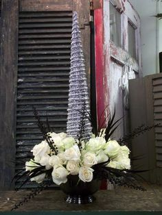 This is an example of fun and different centerpieces we can do. In this arrangement the flowers are all white and cream roses with black feathers and black berries.
