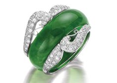 A jadeite abacus ring and a diamond ring guard The intense emerald green jadeite abacus ring, of good translucency with some white mottling, to a fitted ring guard set with brilliant-cut diamonds.