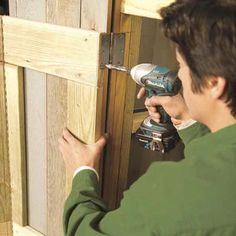 Mark Powers fastening the front doors onto his trash shed
