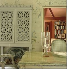 Nicky Haslam ~ his dining room in the country with the painted walls, looking into the library