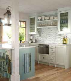Powder blue framed glass door cupboards & tiled wall, open shelves, lantern, wood floor, sky bluewash barn-wood island