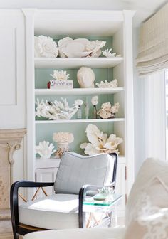 Nautical beach bookcase styling with coral and shells. Shorely Chic