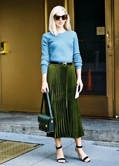 Jane Keltner de Valle wears a light blue sweater, belted midi skirt, cat-eye sunglasses, top-handle bag, and ankle-strap heels