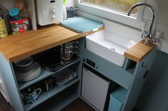 Narrow boat kitchen Canal boat kitchen Narrowboat hire Narrow boat hire Little Blue Boat Small Kitchen Boat Kitchen Modern Narrow boat Modern Canal boat Houseboat Ideas Houseboat interiors Belfast sink open kitchen shelving