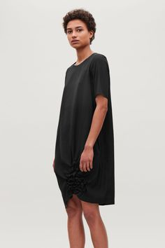 Model side image of Cos dress with smock detail in black