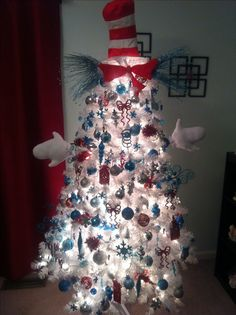 My version of a Cat in the Hat tree. I have different shade of blue, silver, and red ornaments. I also ordered a costume and stuffed the hat to put on top of the tree with the bow tie. I stuffed the gloves with cotton and put them on two branches spray painted black coming out of the tree for arms.