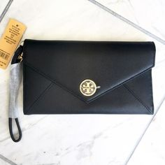 Tory Burch Saffiano Envelope Wristlet BRAND NEW. Tory Burch Saffiano Envelope Wristlet. 100% AUTHENTIC with original packaging. Original protective covers for logo and hardware/ mirror. 1st Edition Robinson Collection Wristlets. Sold out everywhere! This Wristlet is super chic and has everything you need: a makeup mirror, a key ring, a place for lipstick and pen, credit card slots, coin zip, and more! It is surprisingly thin and light. Gold tone hardware and Saffiano leather. Purchased at…