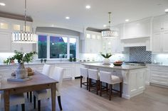 Beautiful transitional kitchen with white cabinets gray granite counter dining island and wood flooring