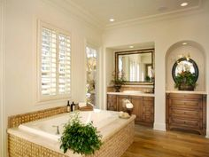 The natural bamboo floor and wicker tub surround gives this bathroom a unique cabana style. Wall niches provide space for a built-in vanity with a wicker backsplash and a dresser while plantation shutters provide privacy from the backyard.