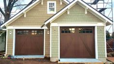 These carriage house garage doors look like real wood but are actually a stainable faux wood composite material that won't rot, warp or crack. Model shown: Clopay Canyon Ridge Collection Limited Edition Series garage doors, Design 22 with arch windows.