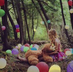 a party in the forest with balloons. lots and lots of balloons. preferably color coordinated.