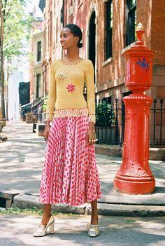 Tami Williams in a gold tassel knit top, Gucci plissé skirt, Gucci jewelry, and…