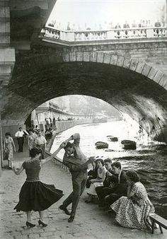 Paris 1952. Reminds me of passing people learning to Tango on the banks of the river when we were once in Paris.