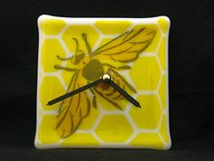 Honey Bee Clock, Bee Wall Clock, Honeycomb Clock, Wall Clock, Beekeeper Gift, Gift for Teacher, Kids Room,. This honeycomb and bee clock is made in white glass, with yellow, orange and black frit (powdered glass) in a honeycomb pattern with a bee. The Clock measures 4.5 x 4.5 inches and the mechanism is a Quartz Clock. It is hand-cut and than fused several times. All my creations are fired at temperatures up to about 1500 degrees and then annealed (slowly cooled) for strength and…