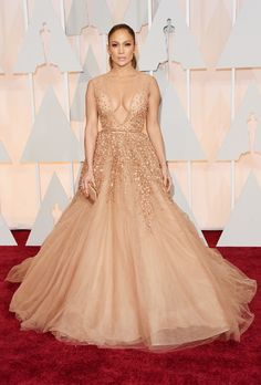 Brides.com: . Jennifer Lopez in Elie Saab. Even one of the sexiest women alive needs to have a princess moment every once in awhile! Case in point: J. Lo, who's practically synonymous with curve-hugging looks, floated down the red carpet in a nude Elie Saab gown featuring layers upon layers of tulle and glitter. Can you say wedding-worthy?