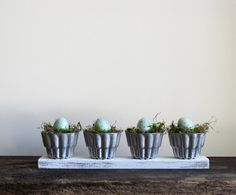 A wonderful Easter display made with an old piece of weathered wood, vintage jello molds, moss and eggs.  Remove the moss and eggs and make an eccentric