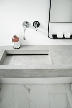 Concrete bathroom counter and metal framed mirror Minimalism
