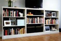 two or three cheap little bookshelves together and trimmed out to be one long pretty bookshelf. Will have to look into it.