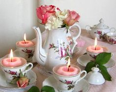 DIY Victorian-tea-party style centrepiece. The teapot becomes a vase. Use an old-fashioned tea set that includes a porcelain teapot with floral designs. You will need some flowers & floating candles. Roses & Carnations were used here, but use whatever matches your tea set design. Make a simple flower arrangement in the teapot. Surround the teapot with tea cups, & place a candle in each one. Charming!