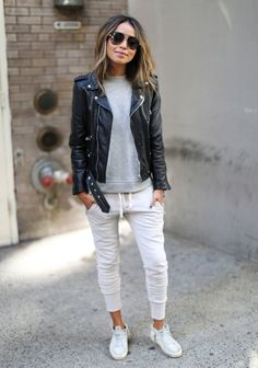 If you're a jeans-and-a-tee kind of gal, you'll like the simple combo of a black leather biker jacket and white jogging pants. Dress down this getup with white leather high top sneakers. Shop this look on Lookastic: https://lookastic.com/women/looks/biker-jacket-crew-neck-sweater-sweatpants/18736 — Grey Crew-neck Sweater — Black Leather Biker Jacket — White Sweatpants — White Leather High Top Sneakers — Black Sunglasses