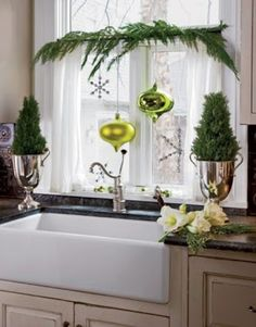 Christmas window idea with a tension rod, greenery and 2 large ornaments