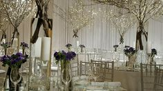 branches of dogwood on mirrortop tables with vases of purple anemone and crystal candlestick