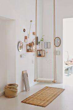 Een indoor schommel geeft een speelse sfeer en dat buitengevoel wat deze kamer weerspiegelt.
