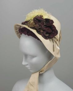 """Bonnet, 1880's France, the Museum of Fine Arts, Boston """" Cream felt bonnet with cream silk ribbon, white ostrich feather and maroon artificial flowers and leaves in front, ribbon ties (yellow discoloration on feather and brim) """""""