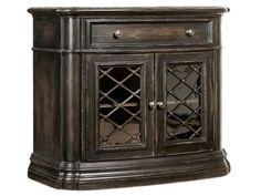 Distinctive bedroom pieces include a nightstand with lattice front, a three-drawer nightstand in the antique white finish with a soft handpainted motif on the front and a round mirror in the white finish with a quatrefoil-shaped inset.