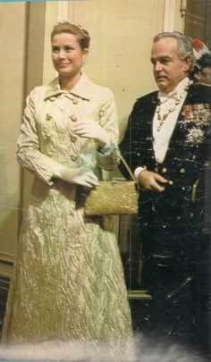 Princess Grace and Prince Rainier attending a Gala. Her ensemble is a design of Marc Bohan of Dior. It is made of silk matelasse, with metallic thread. It is of a silver shade, with raised leaves, with gold embroidery. The ensemble is on display at James Michener Museum.