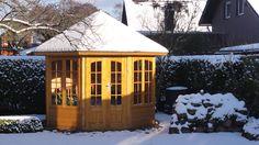 Gartenpavillon aus Holz im verschneiten Garten.