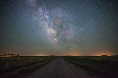 The beautiful Milky Way galaxy lighting the ground from above down this dirt road in Wyoming.
