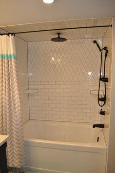 White subway tile shower with grey grout. Black Kingsley fixtures by Moen. Kids' bathroom.