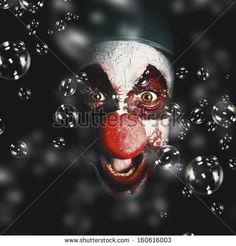 ... clown laughing with evil smile among birthday party bubbles. Crazy
