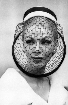 Model is wearing hat with full veil by Balmain, 1959