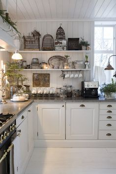 Love the open shelves, the wall board that extends across the ceiling, white cabinets w/black counter top & all the windows. Perfect kitchen. But i'd put black and white floor tiles in.
