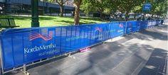 Custom printed mesh banners on crowd control barricades.